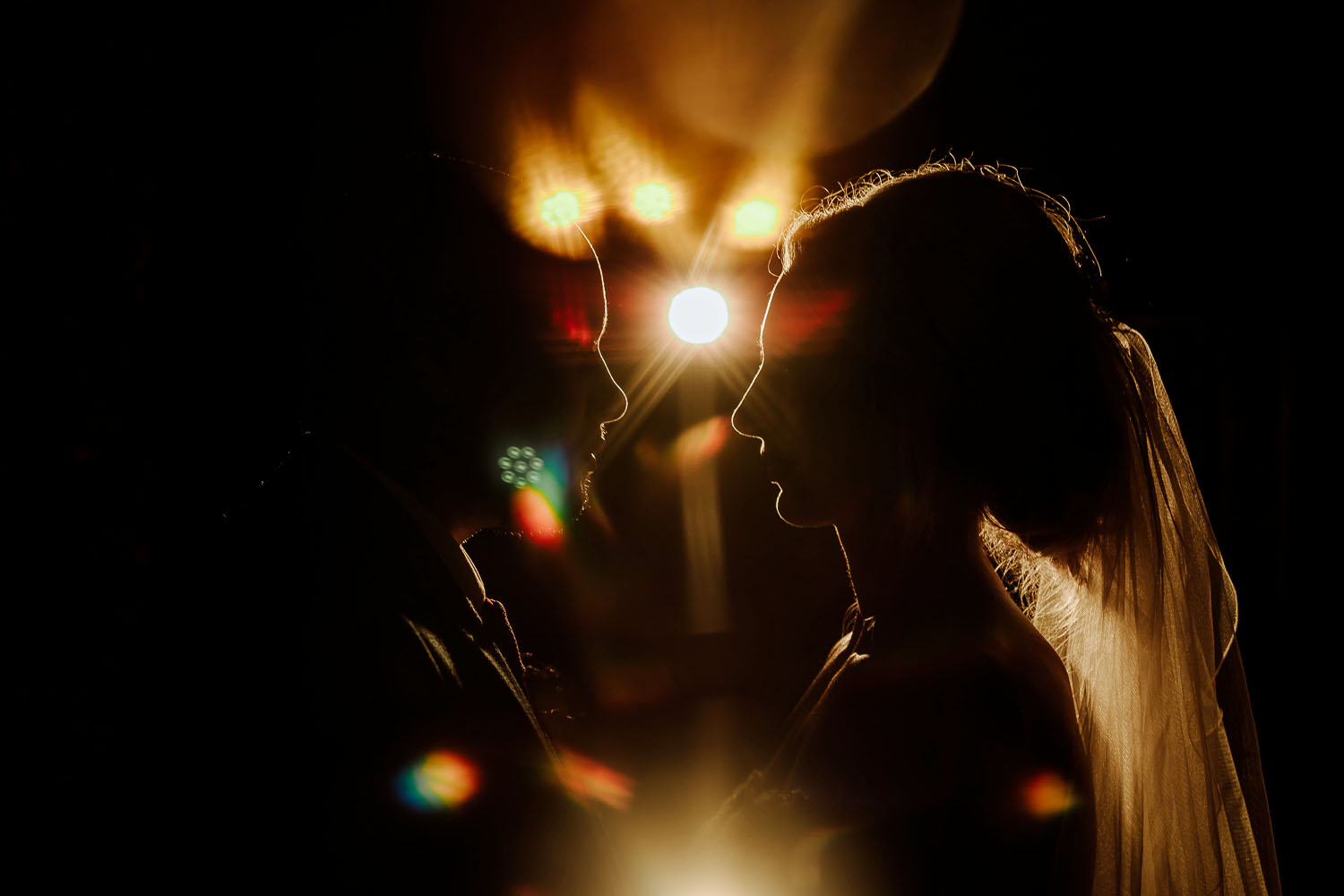 bride and groom creative silhouette with golden light and sparkles