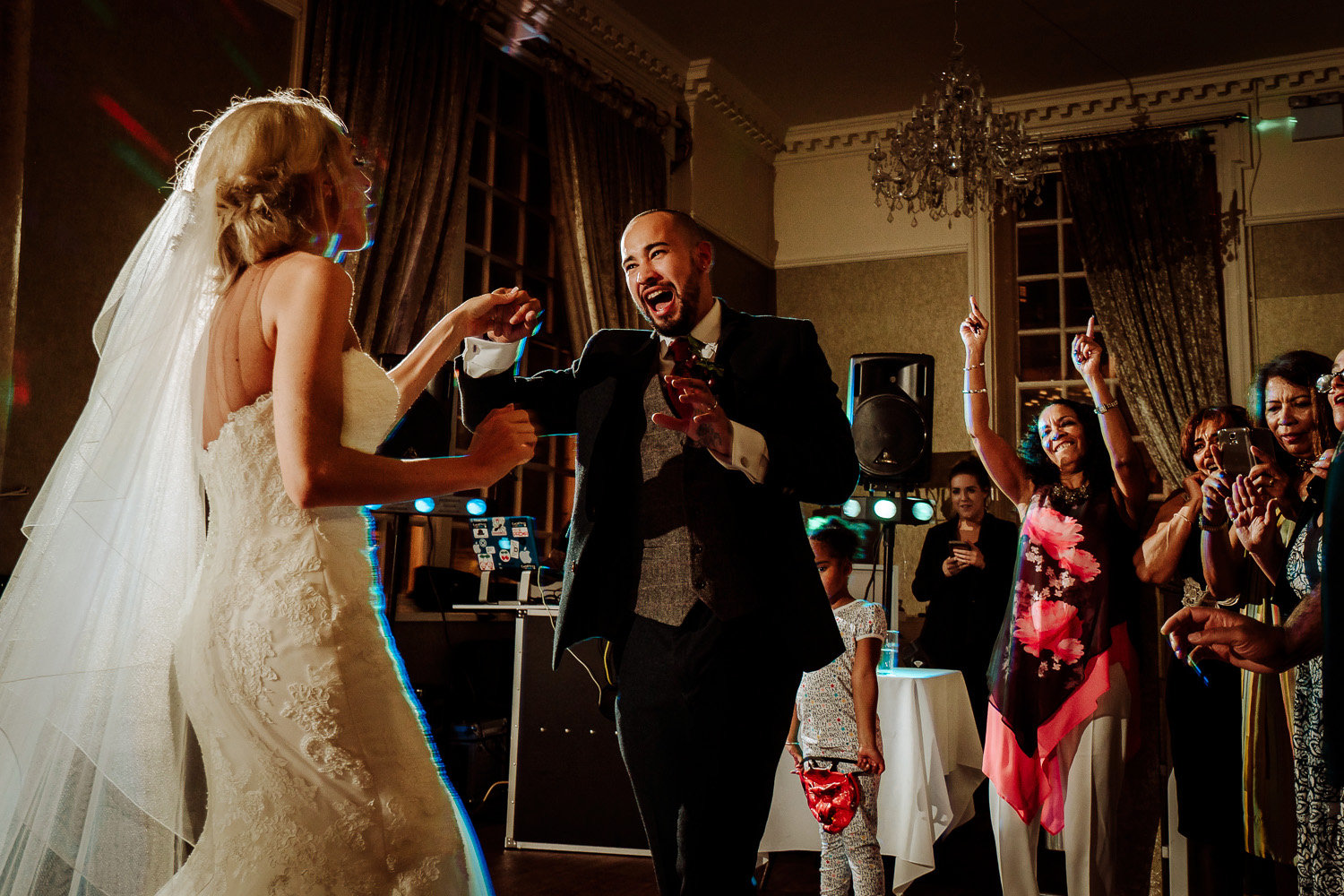groom smiling and dancing with bride as crowd cheer