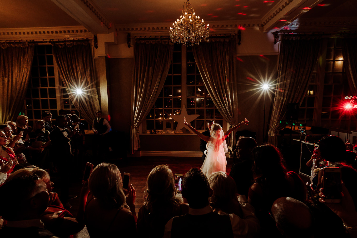 Bride dancing with groom holding her hands up in the air