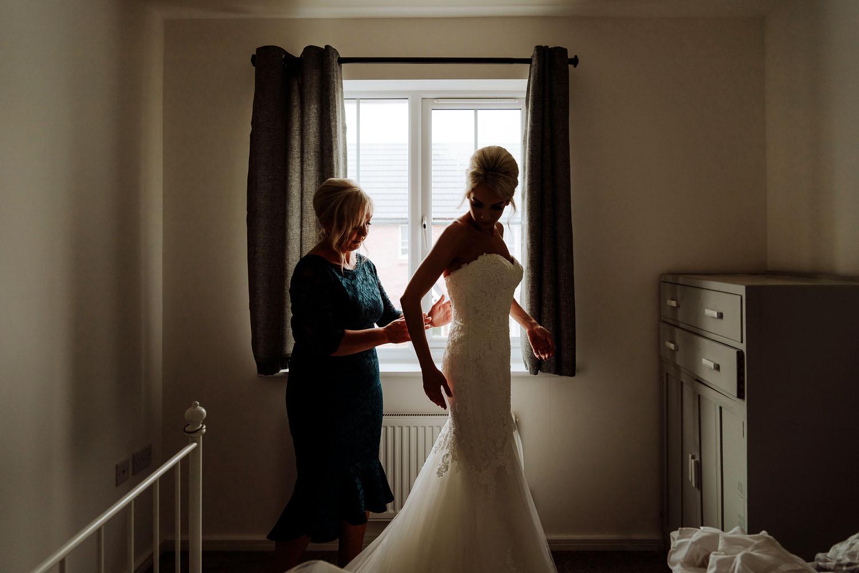 mother of the bride helps wedding dress