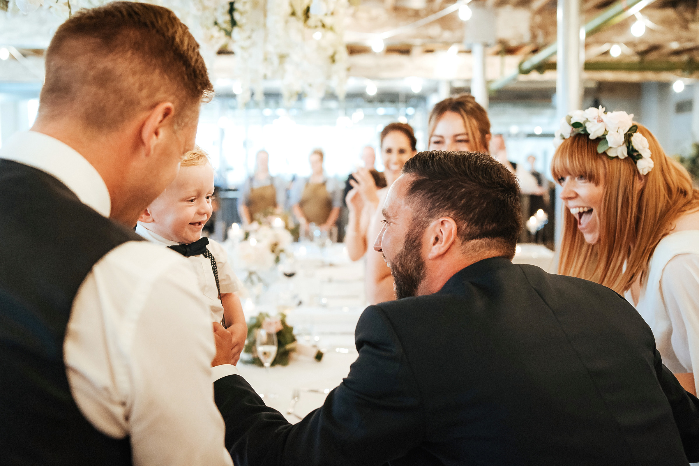 bride and groom laughing with young guest