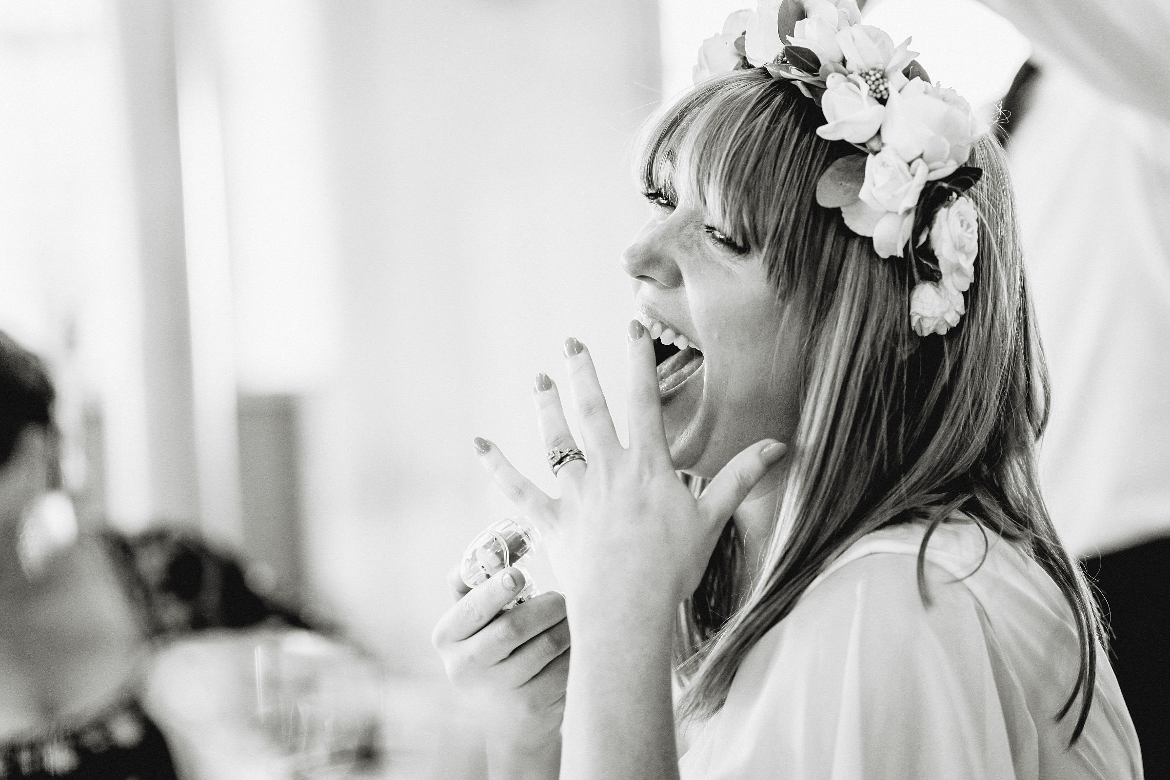 bride laughing and pointing at wedding ring
