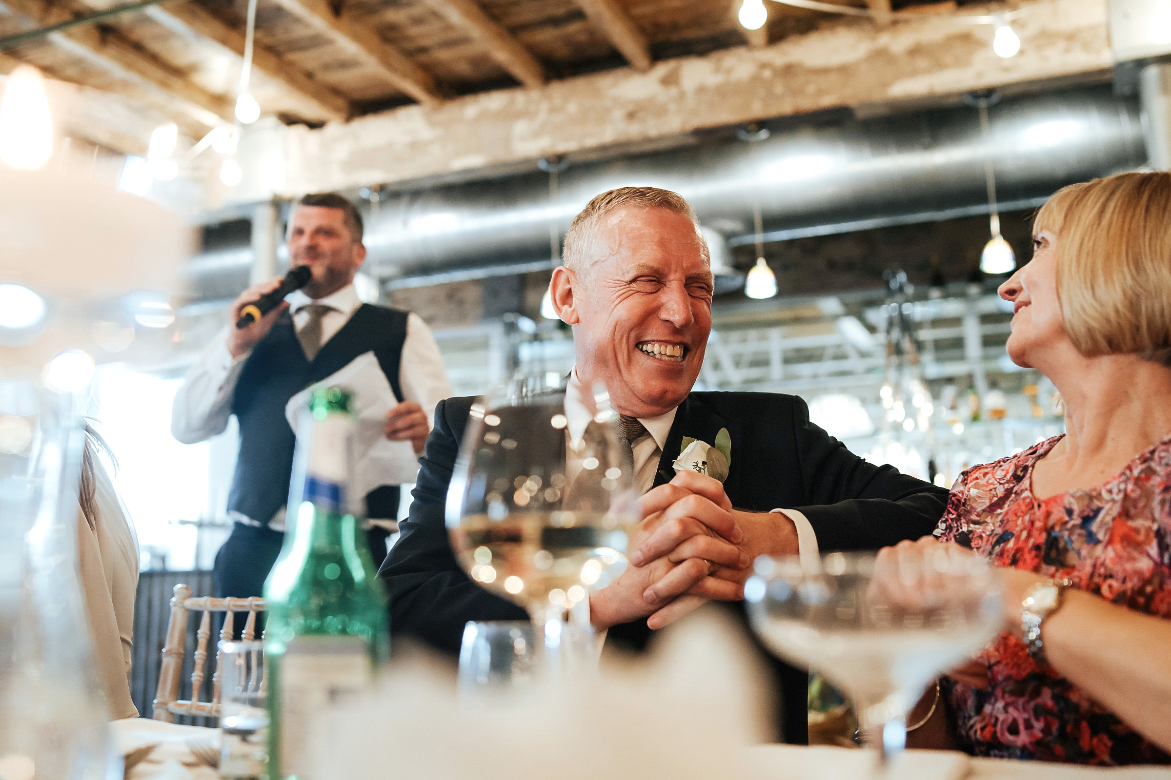 father of the groom laughing at speeches