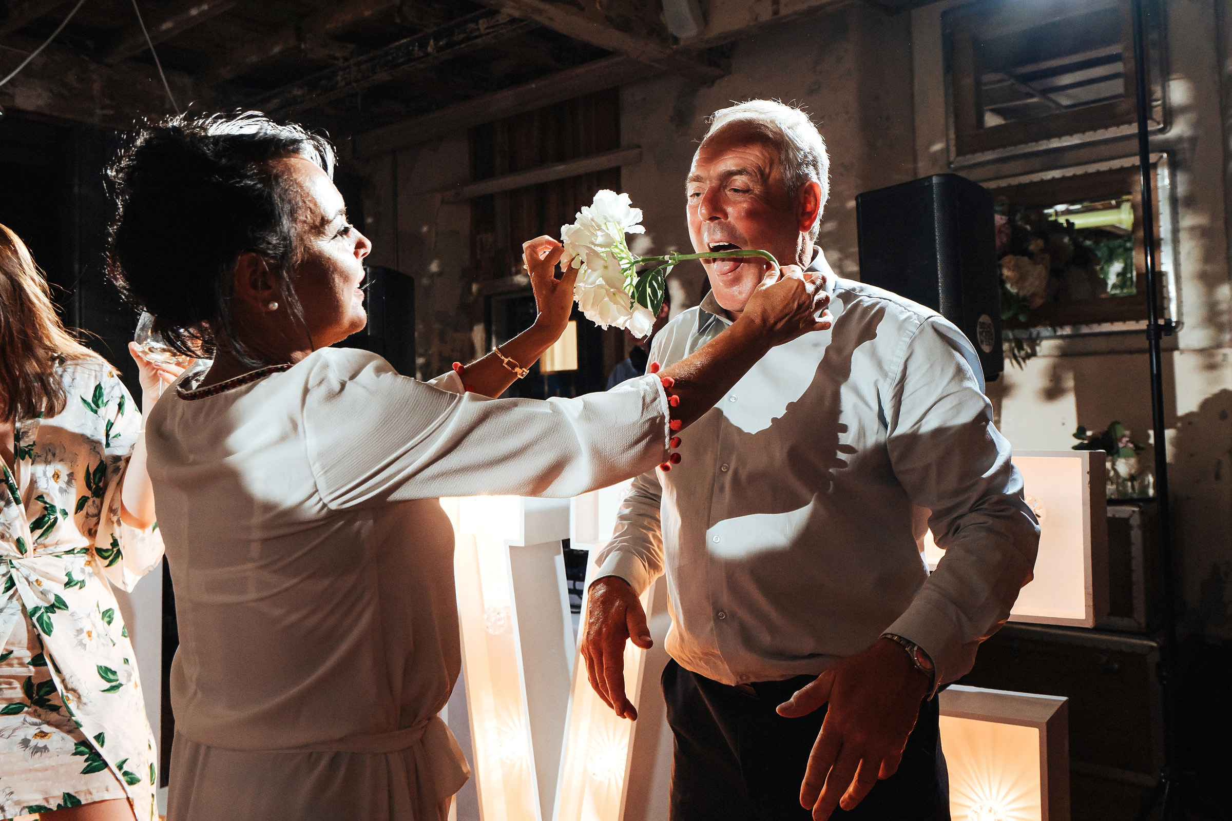 wedding guest takes flower in mouth