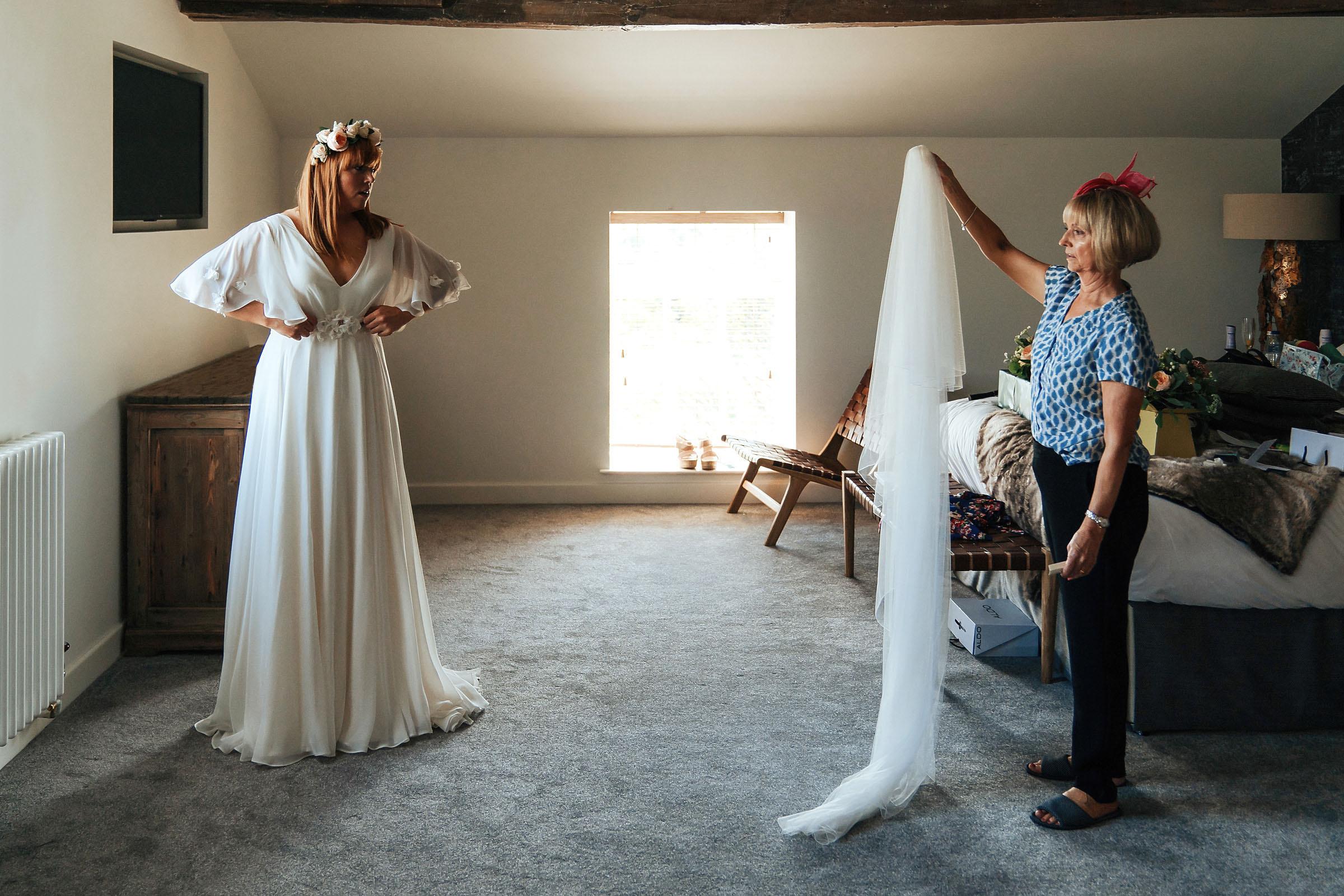 bride looking at wedding veil in bridal suite