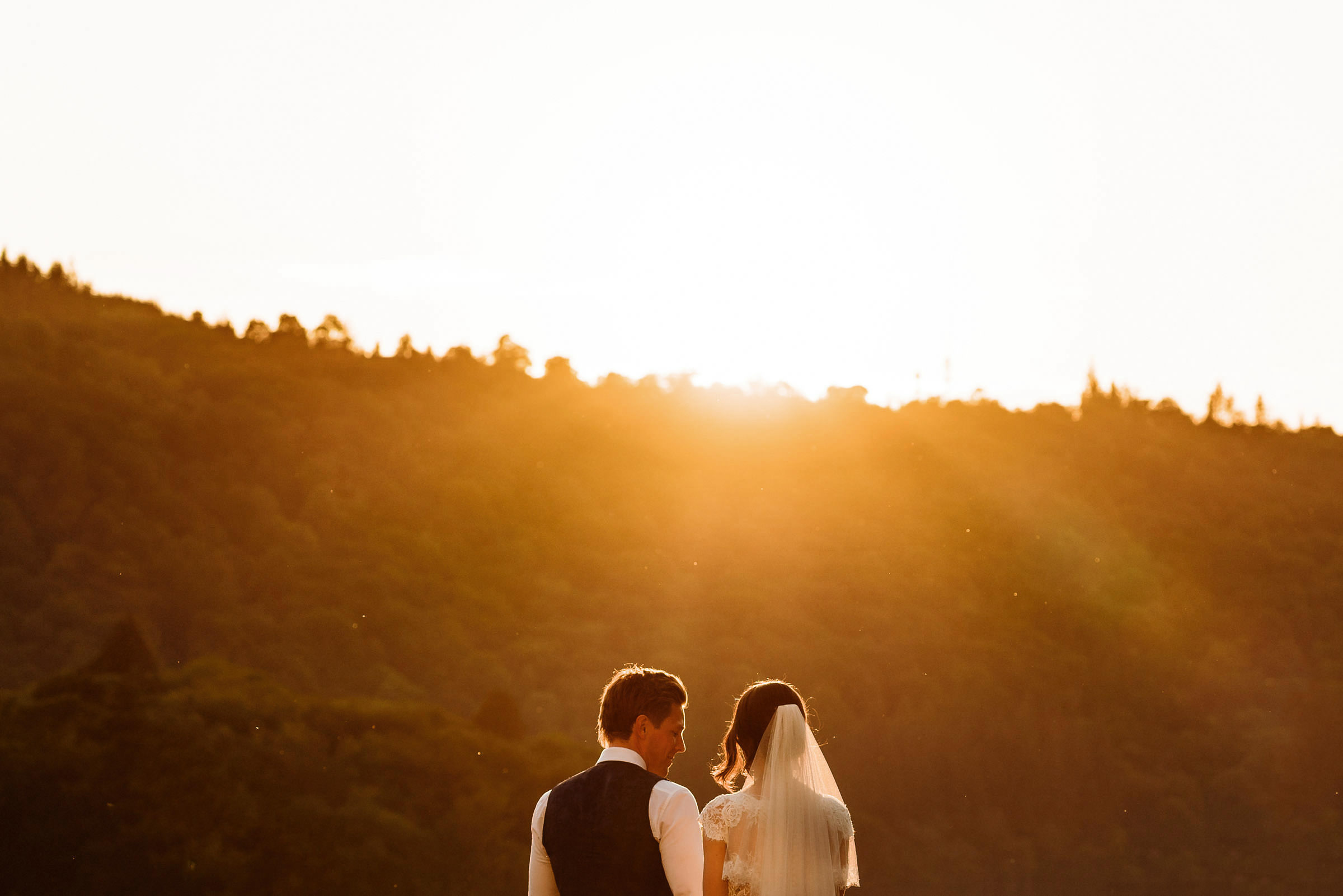 bride and groom standing in sunset