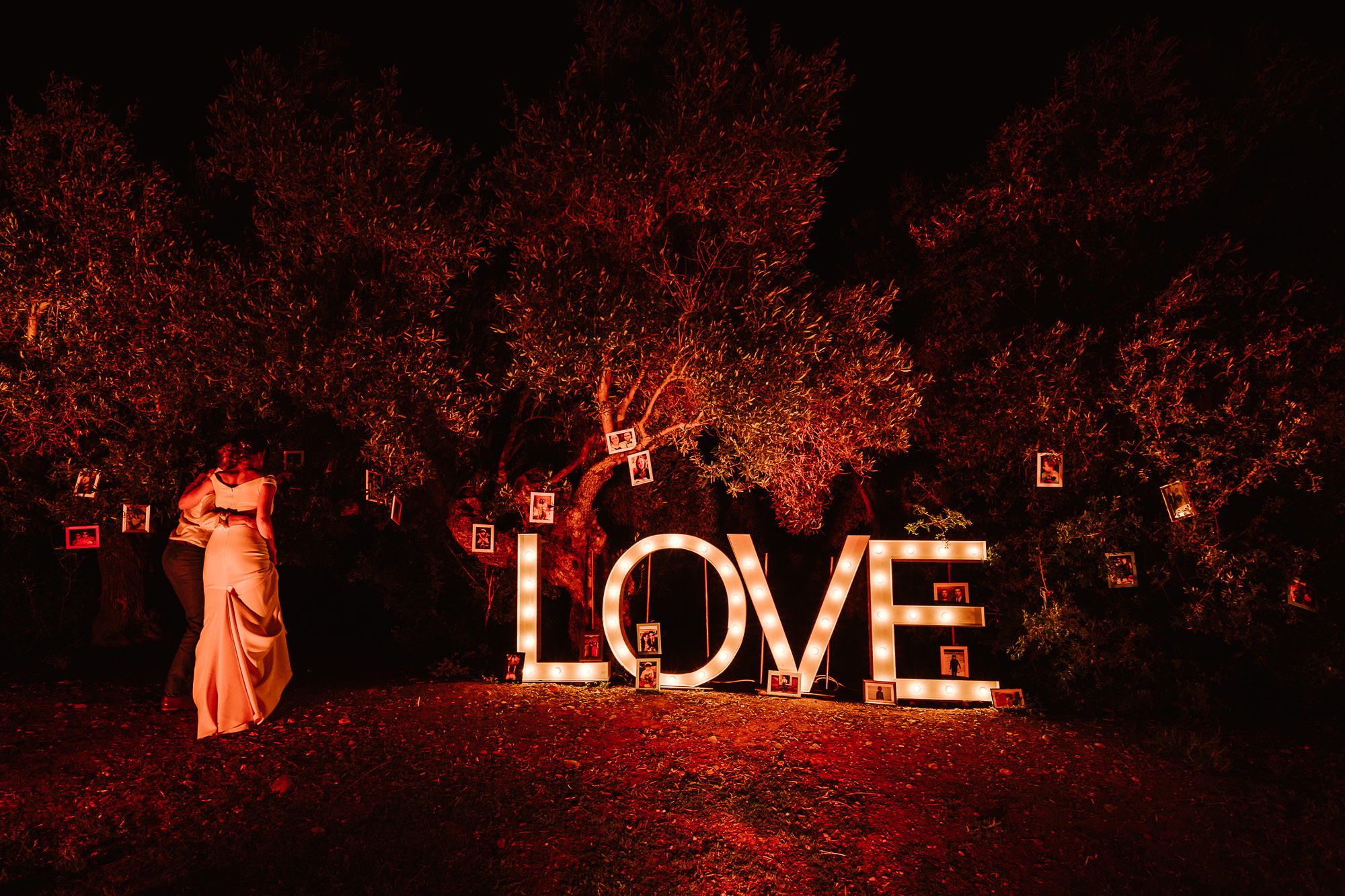 bride and groom walking towards neon LOVE sign