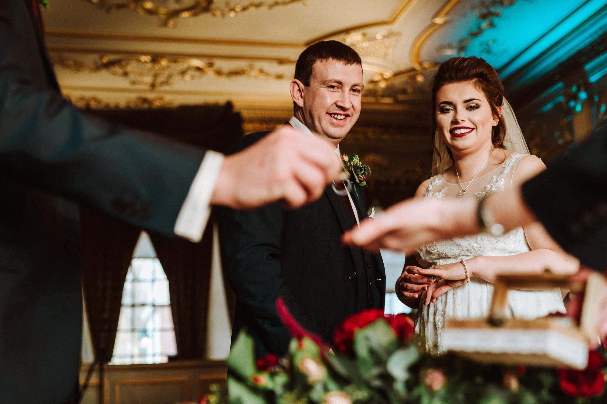 best man hands wedding ring to celebrant