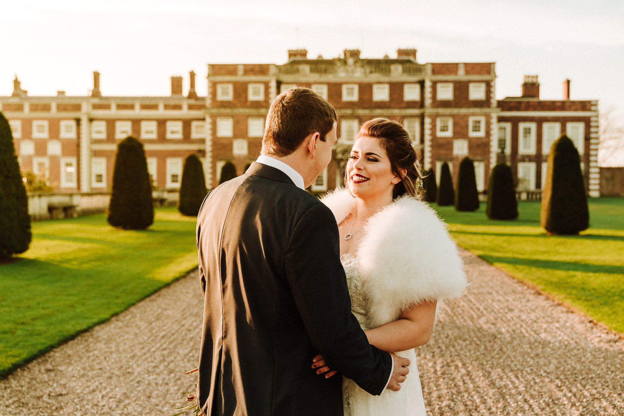 bride and groom hugging outside Knowsley Hall