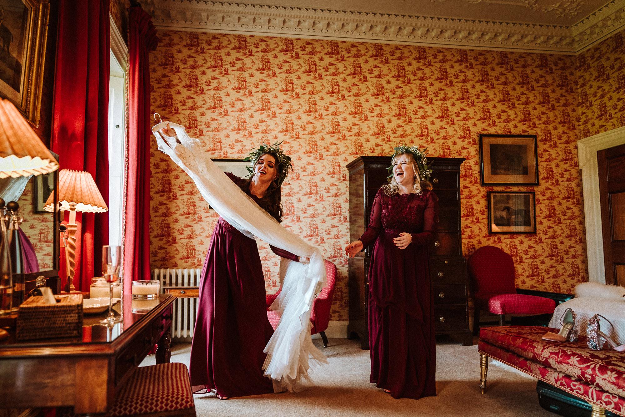 bridesmaids carrying wedding dress