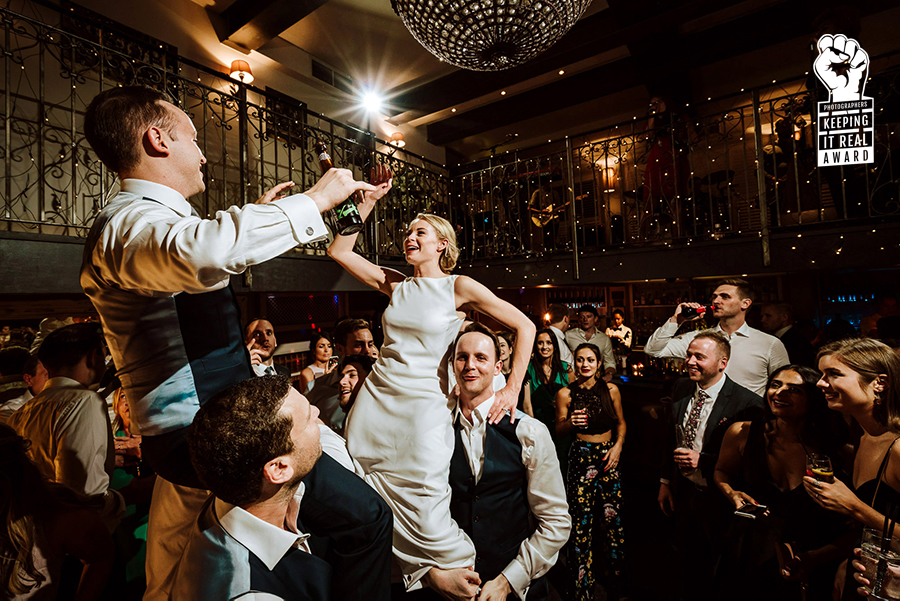 bride and groom lifted by guests on dance floor