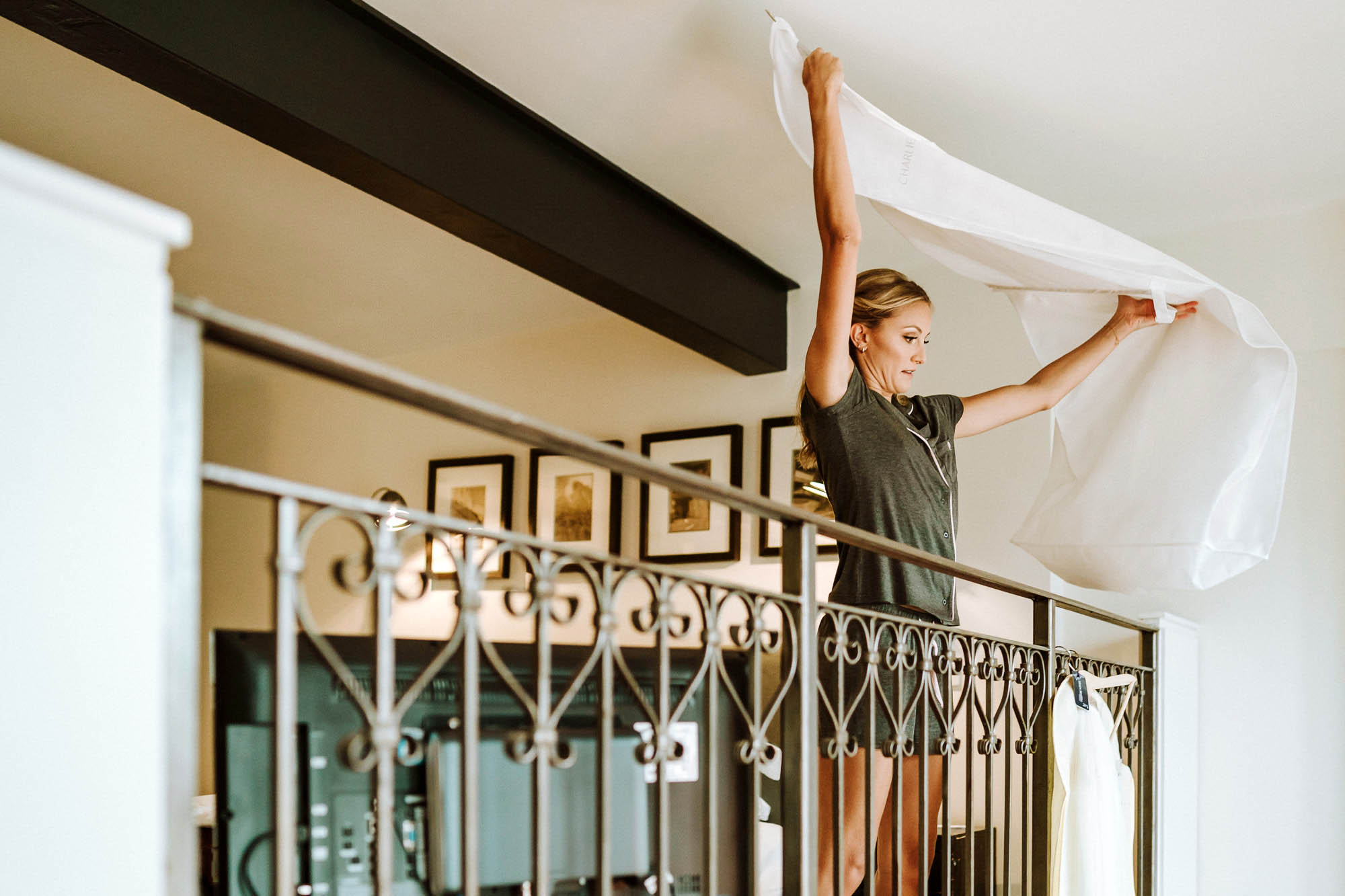 bridesmaid hanging wedding dress over balcony