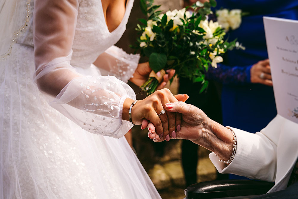 Bride grasping grandmothers hand