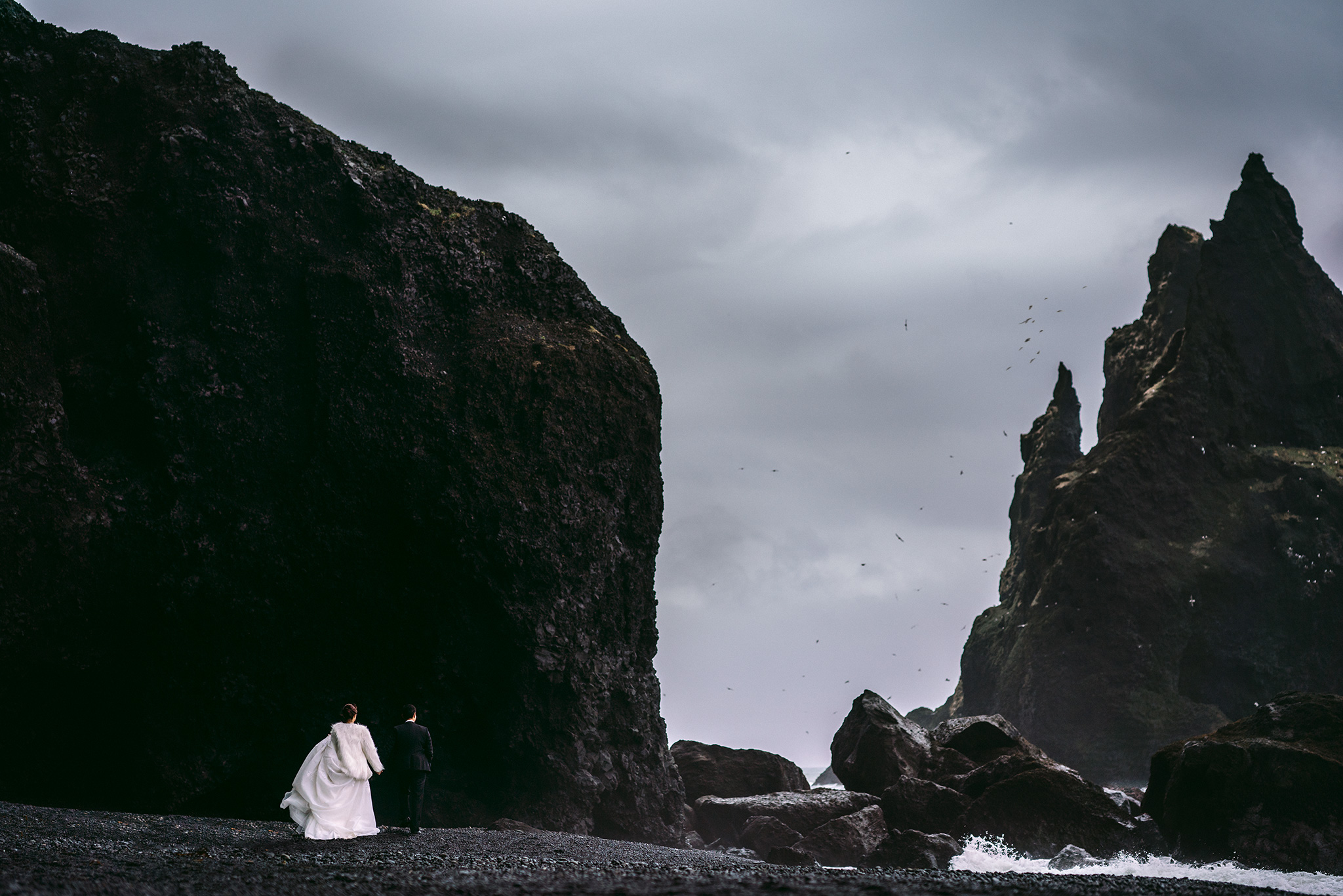 bride and groom walking iceland beach