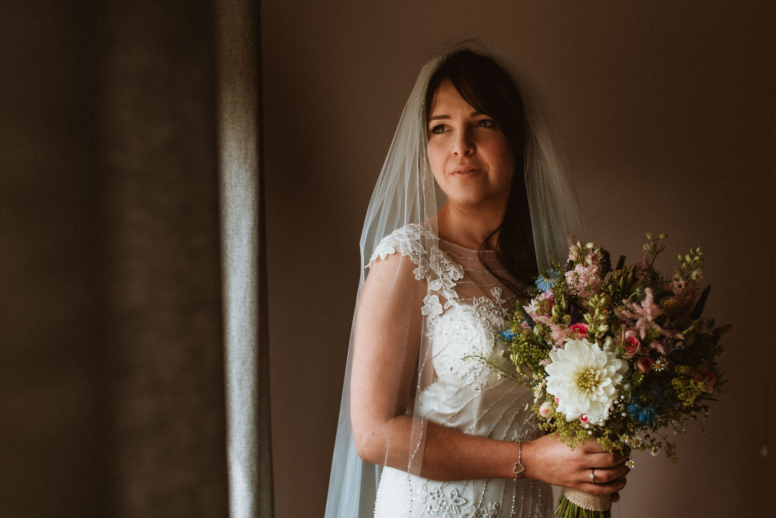 beautiful bride looking out of mere court window