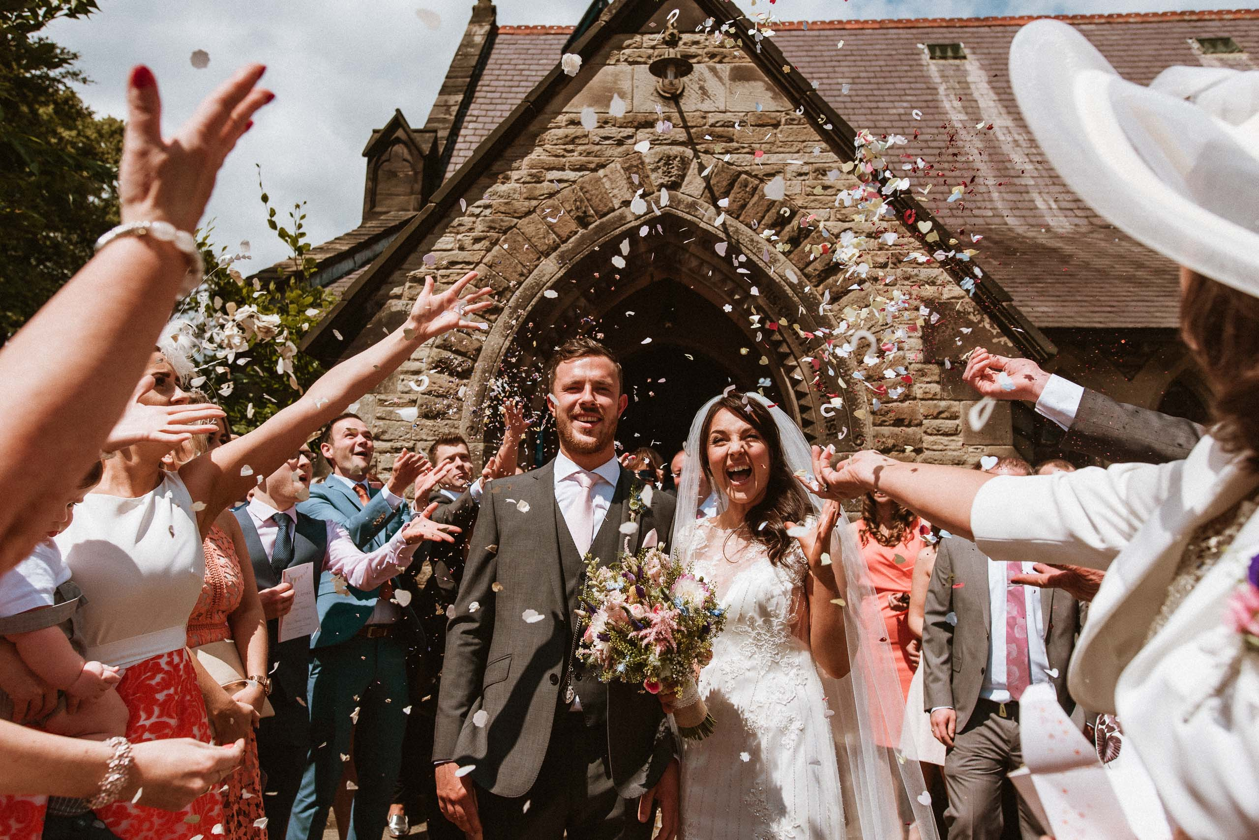 bride and groom laughing as guests throw confetti