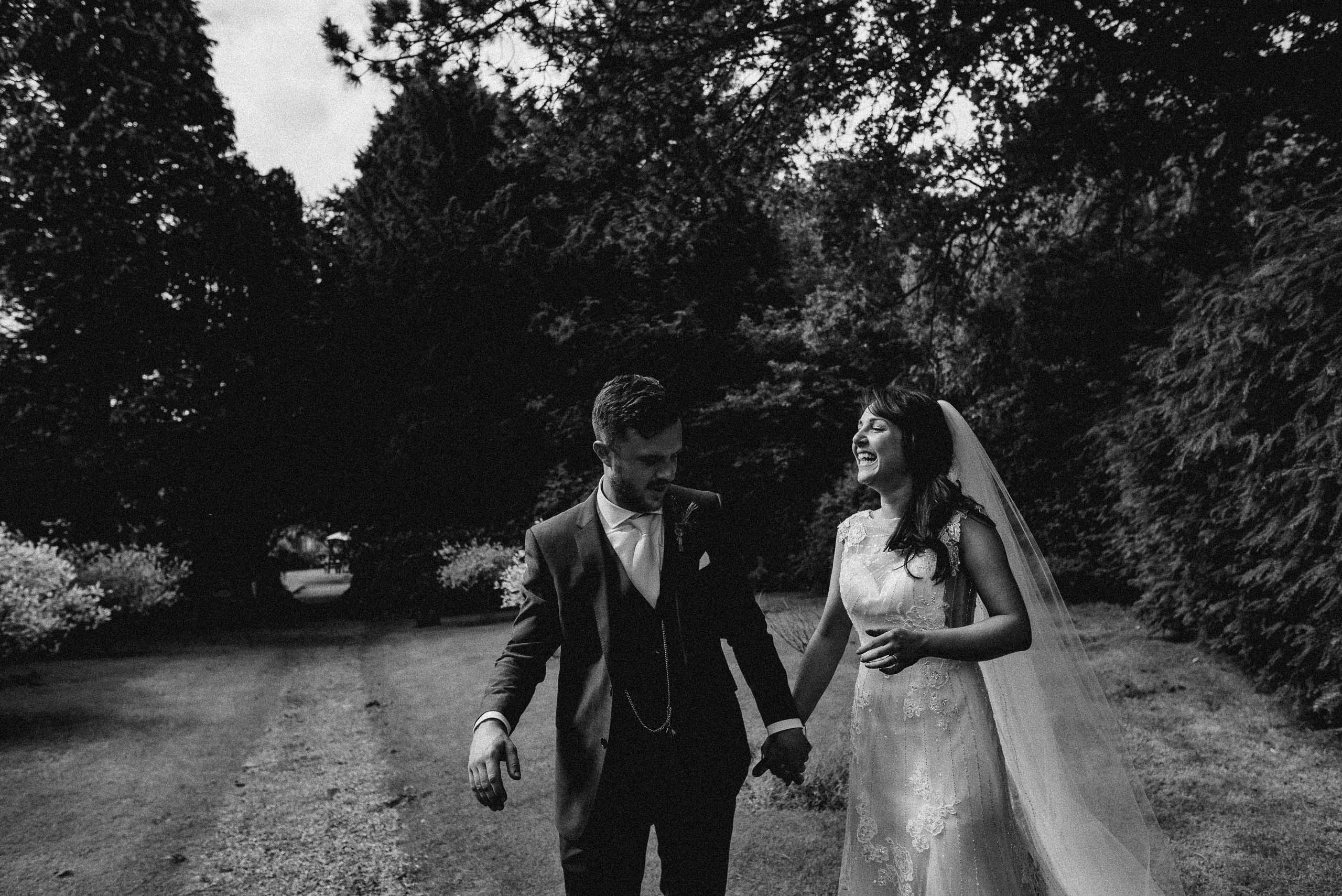 bride laughs as she walks holding hands with groom