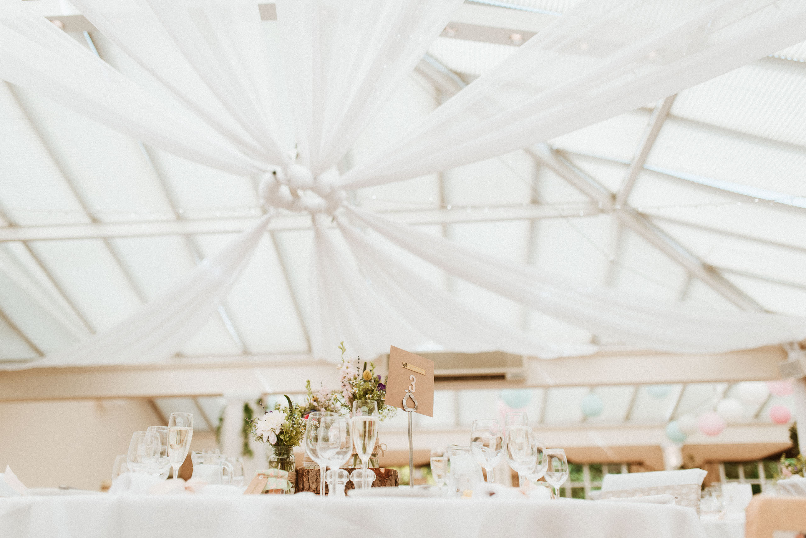 table decorations under white ceiling drapes