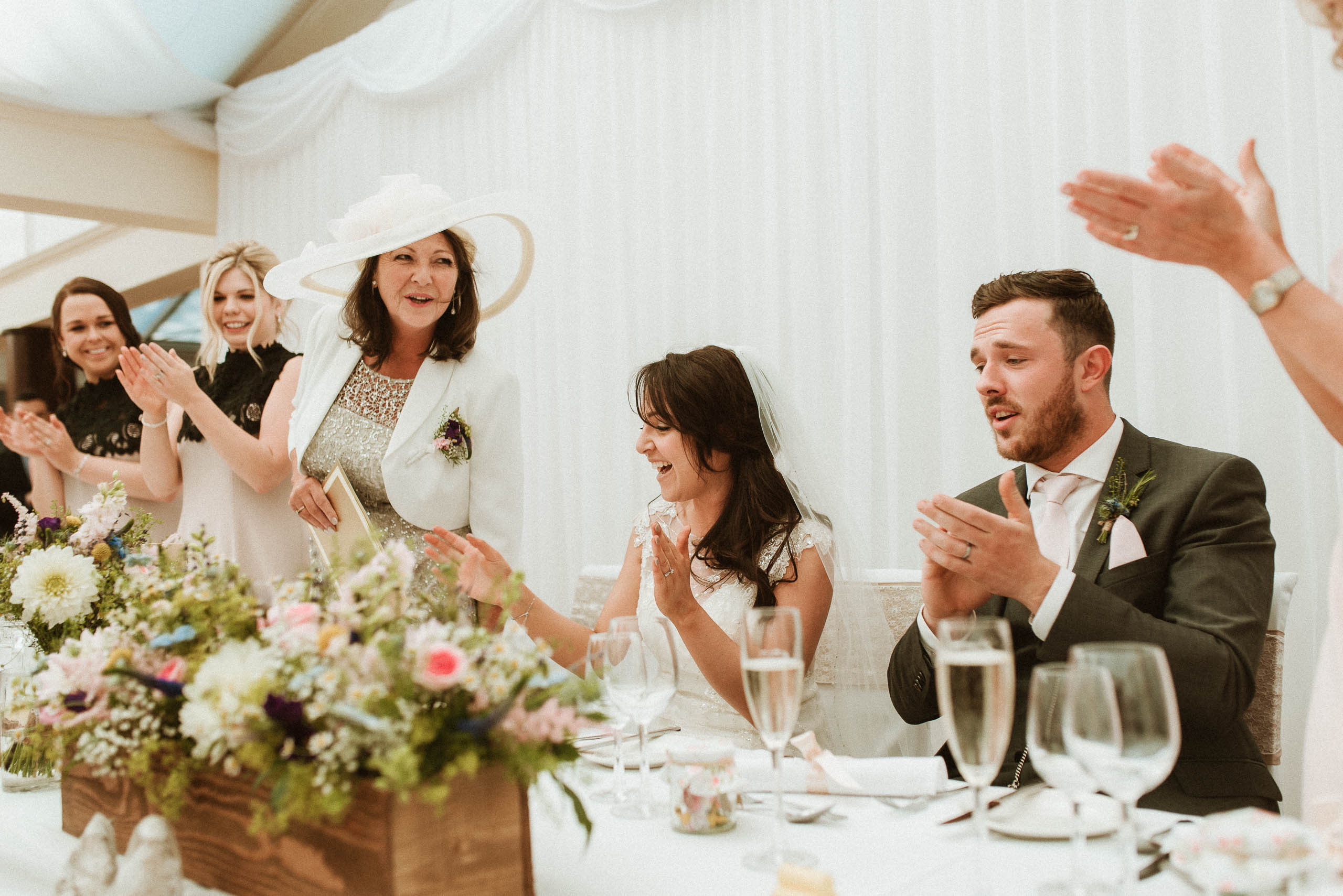 guests applaud bride and groom as they sit down at head table