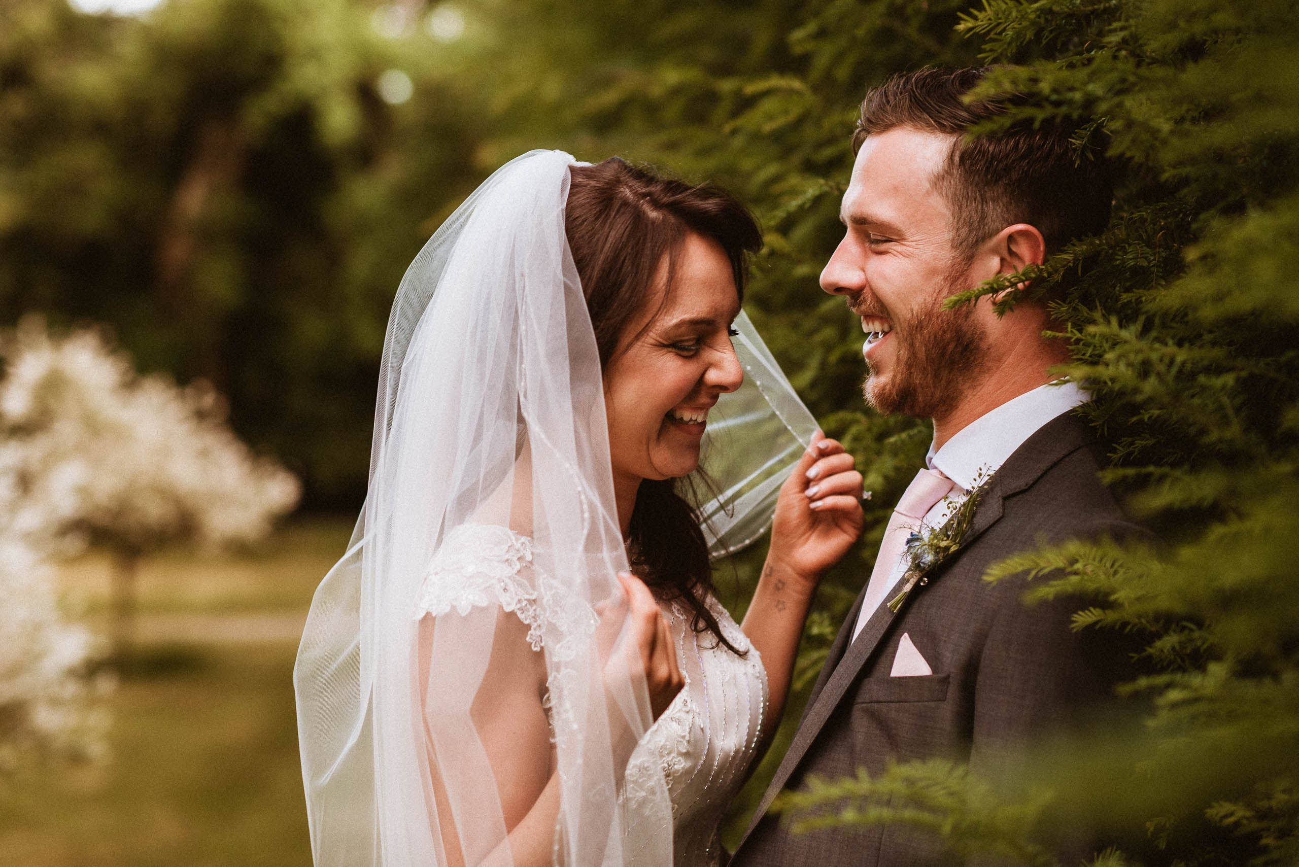 bride and groom laughing in the bushes