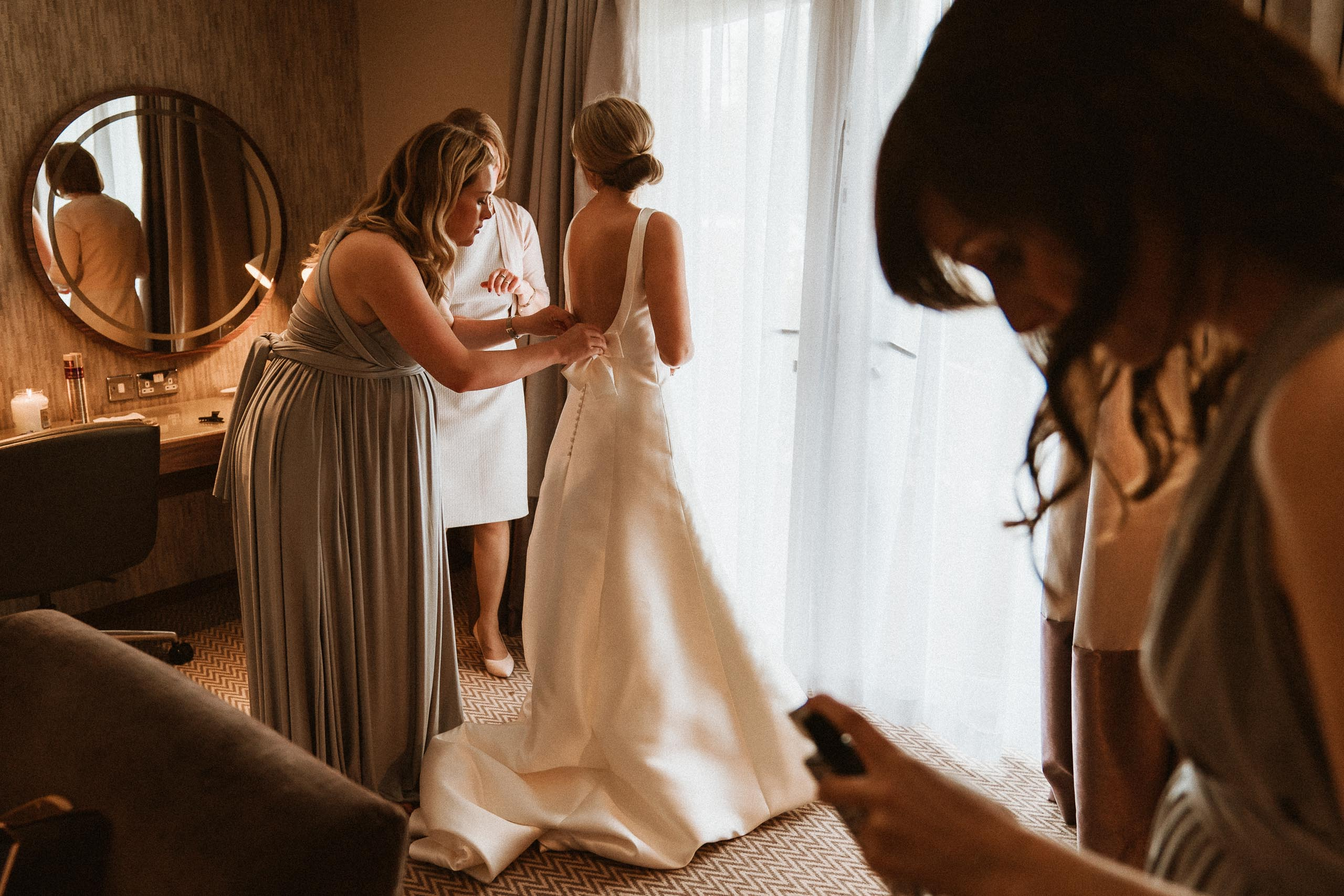 bride getting into wedding dress with bridesmaids helping