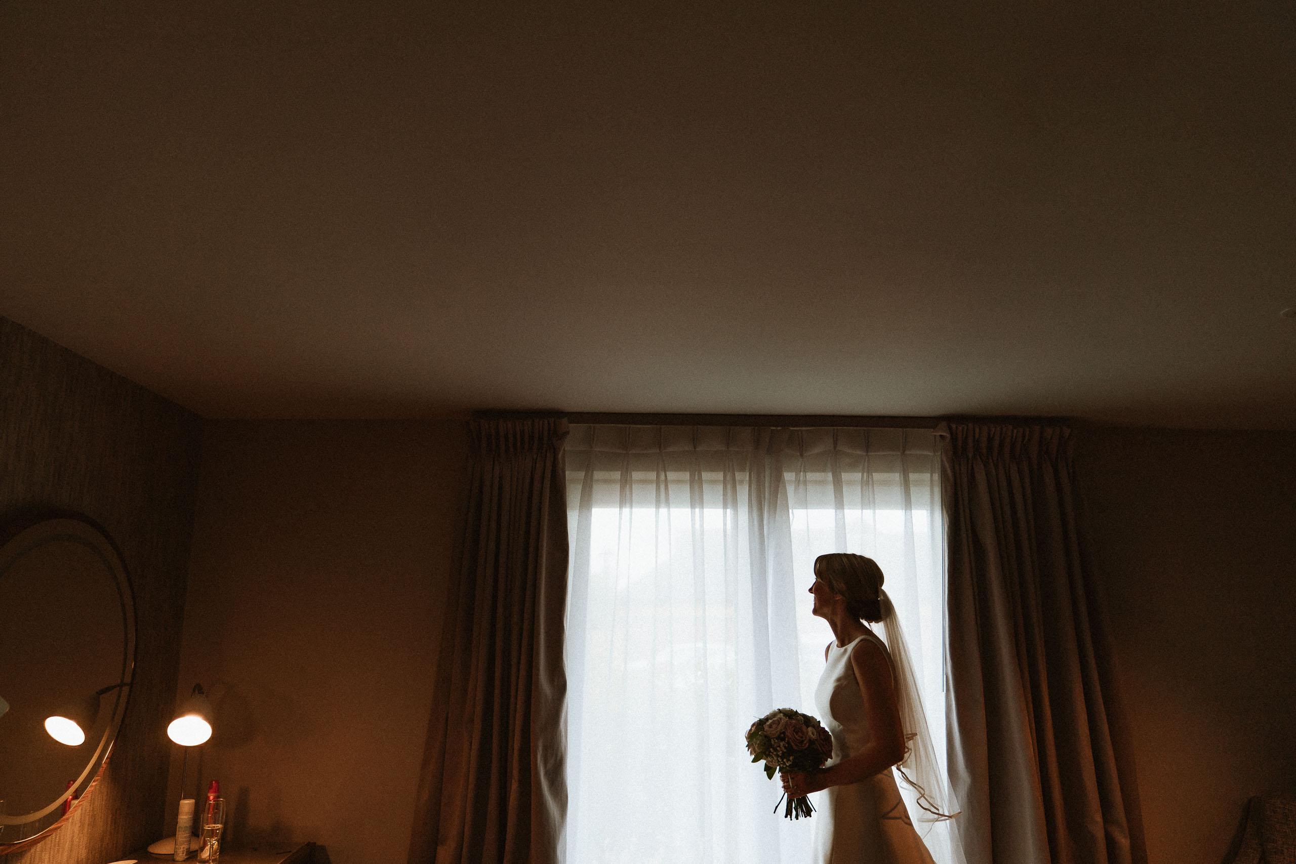 bride silhouetted against bedroom window