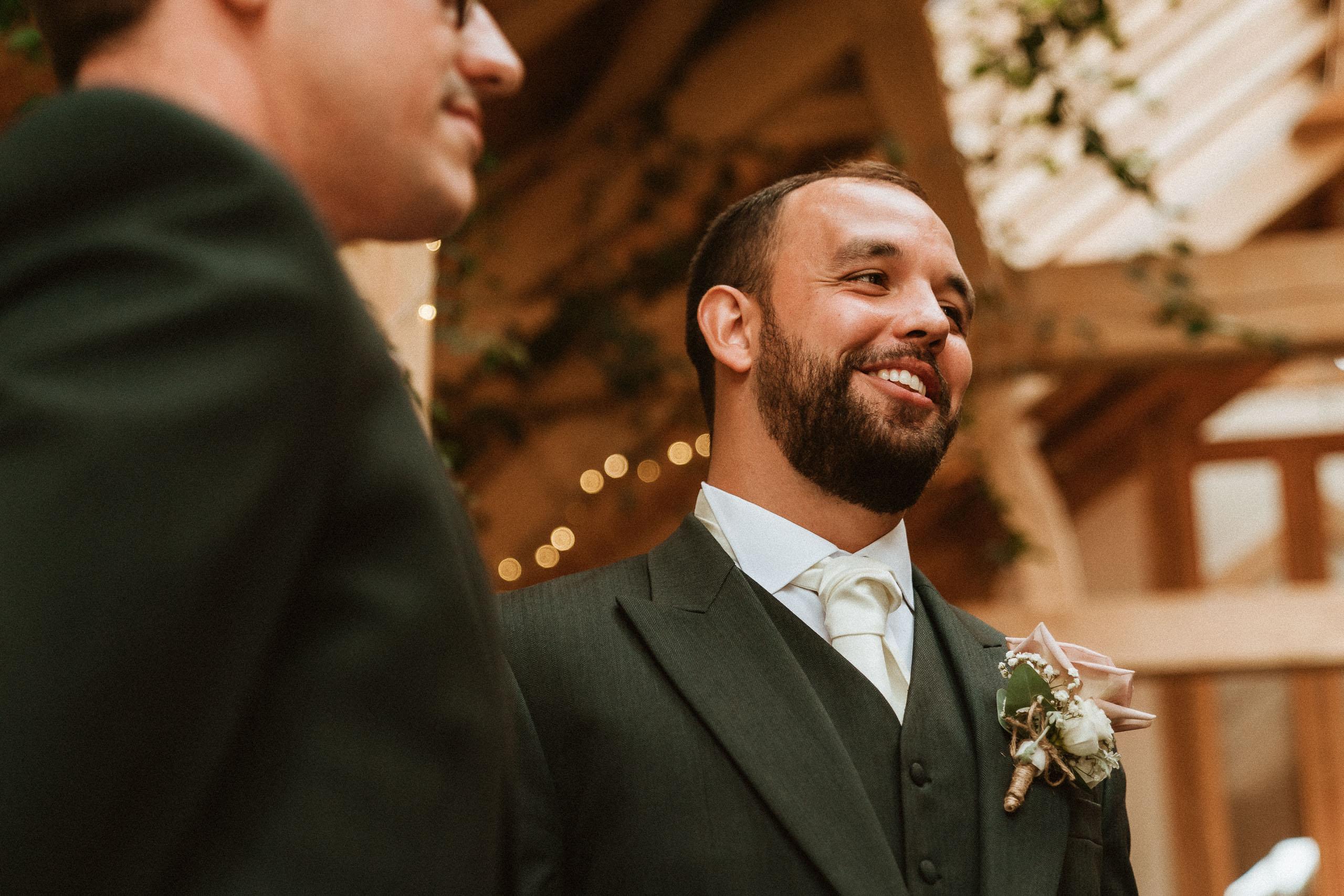 groom waiting inside barn at Oak tree of Peover
