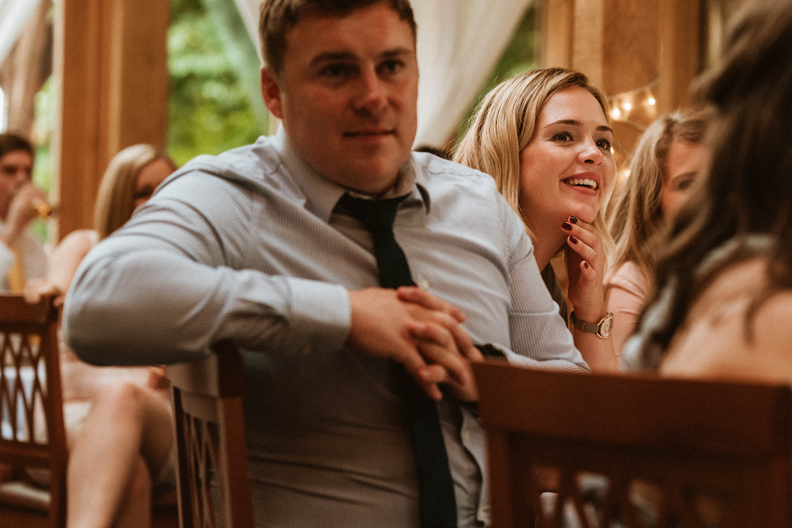 female wedding guest smiling at speeches