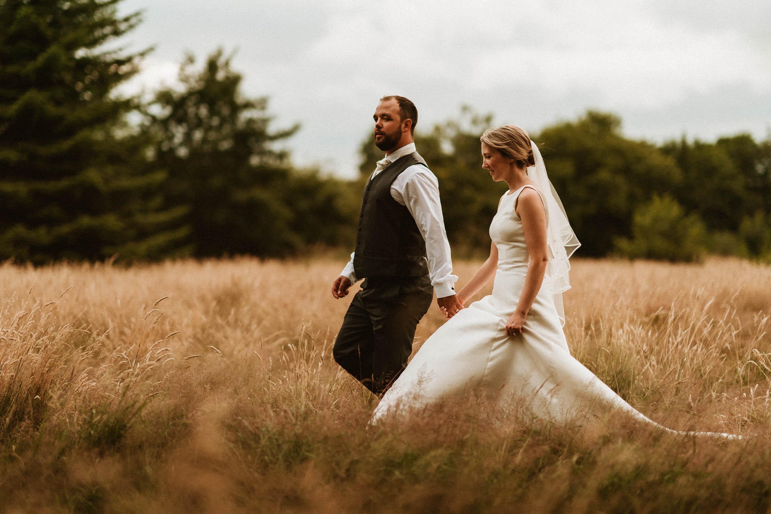 bride and groom walking through tall golden grass
