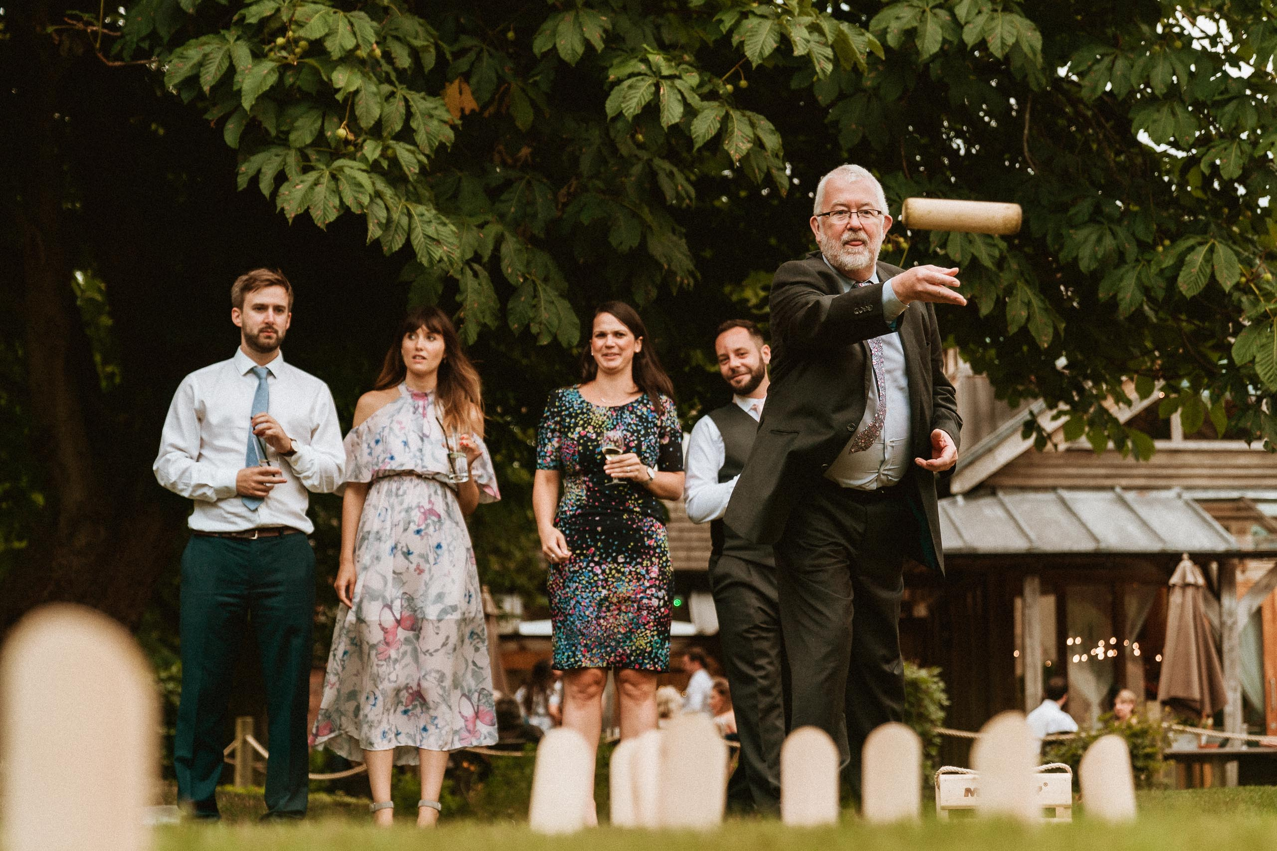 bearded man playing throwing game outside wedding venue
