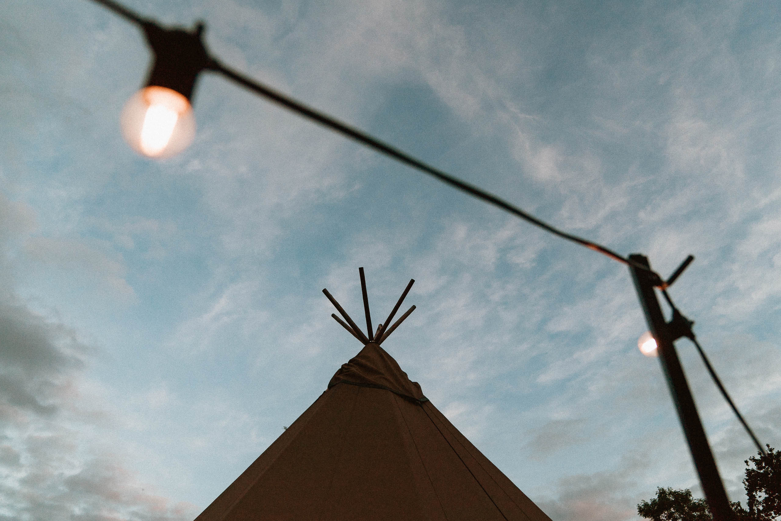 top of a tipi tent framed with fairy lights