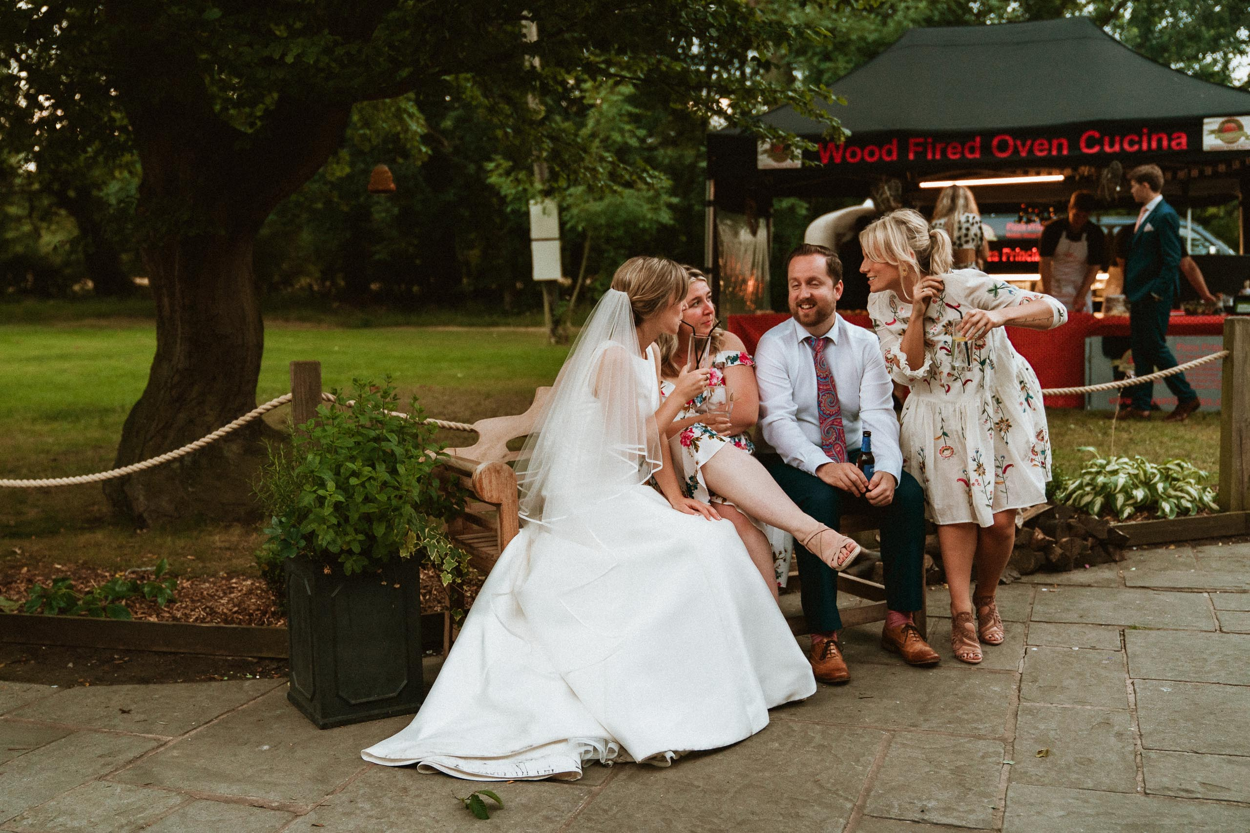 bride sitting on bench with guests near mobile pizza oven