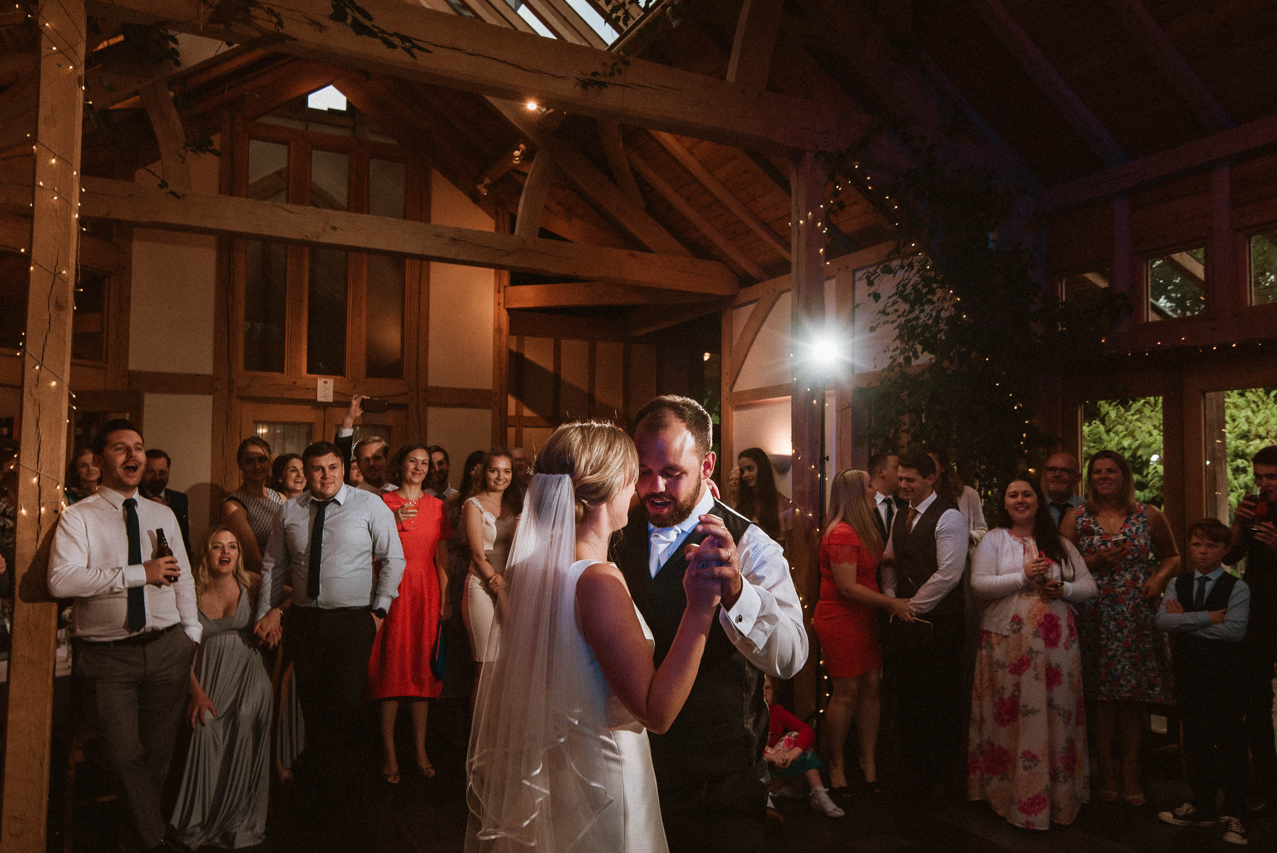 first dance of bride and groom with guests watching